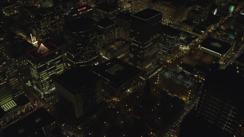 6K stock footage aerial video flying away from downtown buildings at night in Downtown Portland, Oregon, reveal KOIN Center Aerial Stock Footage   AX155_405