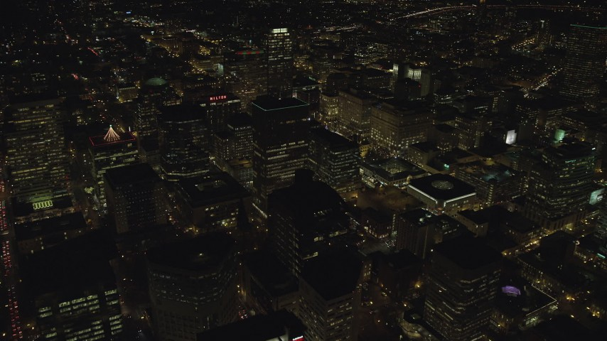 6K stock footage aerial video flying by high-rises, skyscrapers and the Hilton Portland at night in Downtown Portland, Oregon Aerial Stock Footage | AX155_408