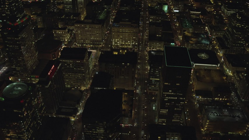 6K stock footage aerial video flying by and reverse view of high-rises, skyscrapers and downtown city streets at night in Downtown Portland, Oregon Aerial Stock Footage | AX155_409