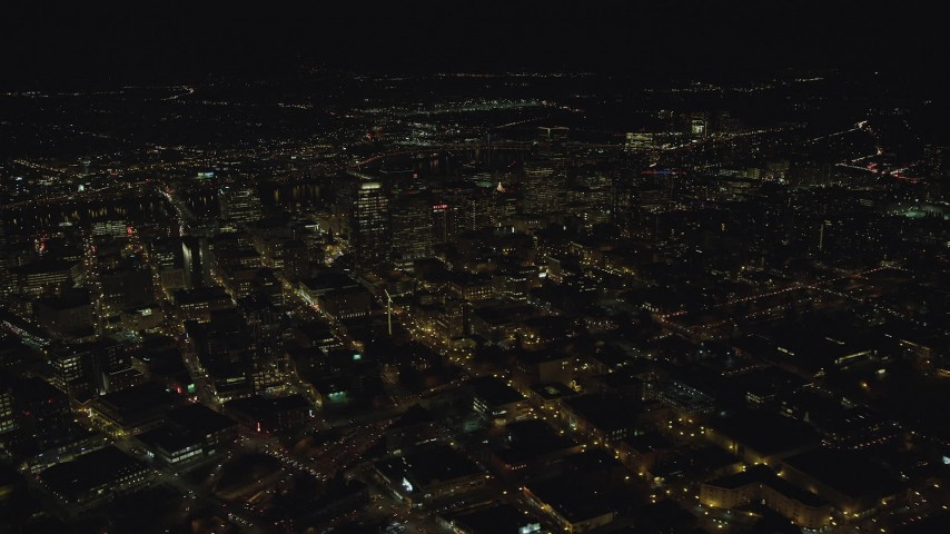 An approach to high-rises and skyscrapers at night in Downtown Portland, Oregon Aerial Stock Footage | AX155_412