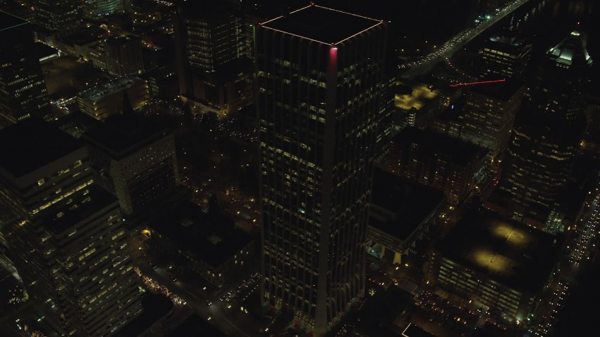 6K aerial video orbiting Wells Fargo Center to reveal busy city streets and KOIN Center at night in Downtown Portland, Oregon Aerial Stock Footage | AX155_415