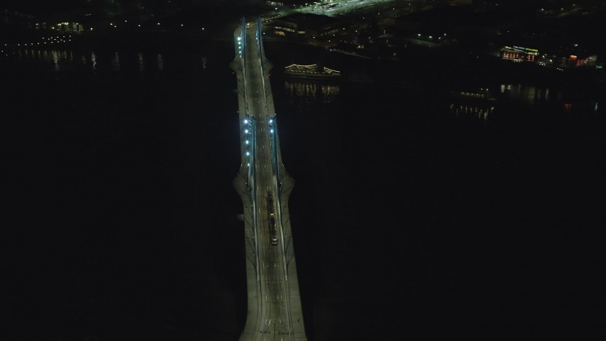 6K stock footage aerial video orbiting Tilikum Crossing bridge as a commuter train crosses the span at night in South Portland, Oregon Aerial Stock Footage | AX155_416
