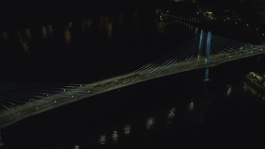 6K stock footage aerial video tracking commuter trains crossing the Tilikum Crossing bridge at night in South Portland, Oregon Aerial Stock Footage | AX155_417