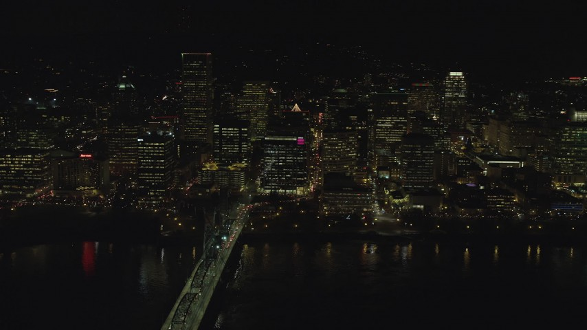 6K stock footage aerial video passing waterfront skyscrapers by Hawthorne Bridge at night in Downtown Portland, Oregon Aerial Stock Footage | AX155_419