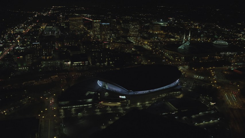 6K stock footage aerial video flying by Moda Center and office buildings at night in Northeast Portland, Oregon Aerial Stock Footage | AX155_430