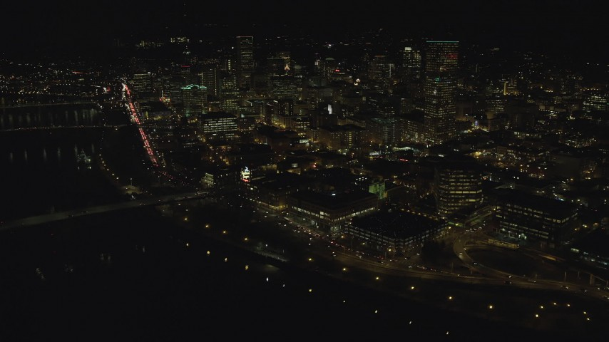 6K aerial video of kyscrapers, high-rises, and White Stag sign seen from Burnside Bridge at night, Downtown Portland, Oregon Aerial Stock Footage | AX155_431