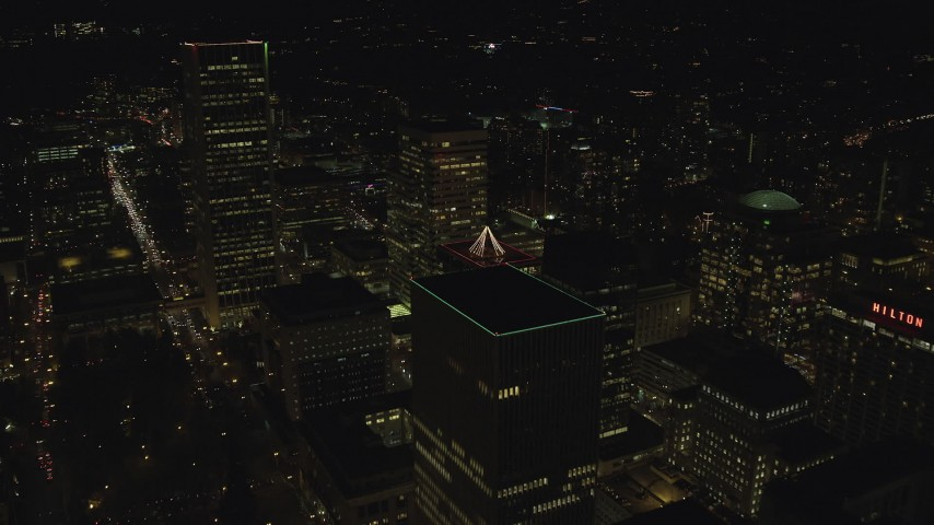 6K stock footage aerial video flying over skyscrapers to reveal and approach Portland State University at night, Downtown Portland, Oregon Aerial Stock Footage | AX155_434