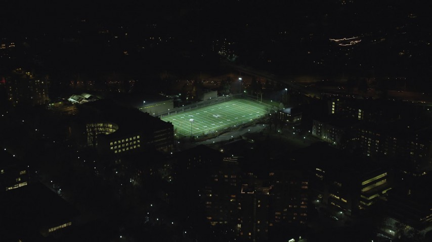 Approach football practice at Portland State University sports field at night, Downtown Portland, Oregon Aerial Stock Footage | AX155_435