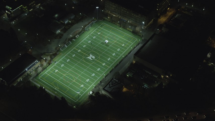 6K stock footage aerial video of a reverse view of football practice at Portland State University sports field at night, reveal I-405, Downtown Portland, Oregon Aerial Stock Footage | AX155_437