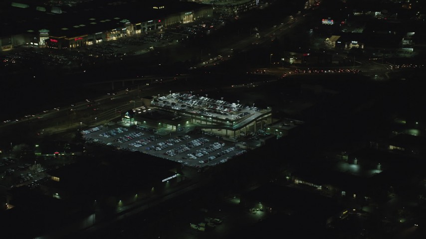 6K stock footage aerial video flying by a packed parking garage at night in Tigard, Oregon Aerial Stock Footage | AX155_450