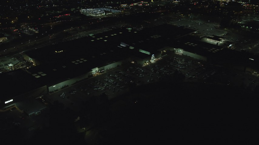 6K stock footage aerial video orbiting the side of Washington Square shopping mall at night in Tigard, Oregon Aerial Stock Footage | AX155_454
