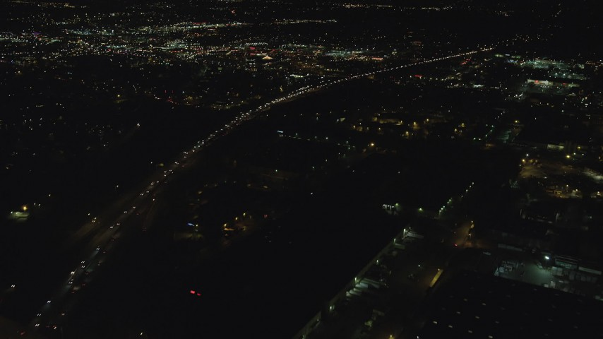 6K stock footage aerial video flying over warehouse buildings, approach Highway 217 and Beaverton Town Square at night, Beaverton, Oregon Aerial Stock Footage | AX155_464