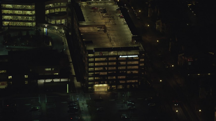 6K stock footage aerial video flying by a hospital parking garage at night in Hillsboro, Oregon Aerial Stock Footage | AX155_473
