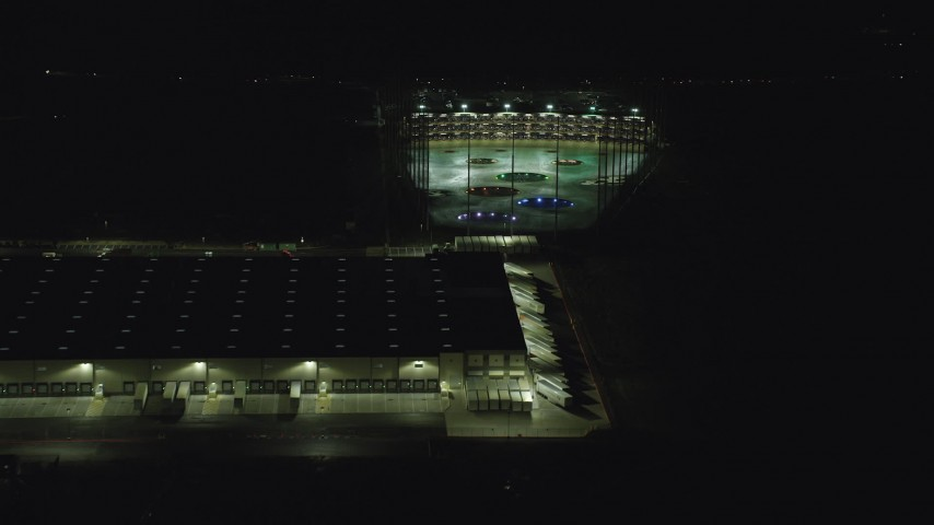 6K stock footage aerial video passing a warehouse building and a Topgolf course in Hillsboro, Oregon at night Aerial Stock Footage | AX155_475