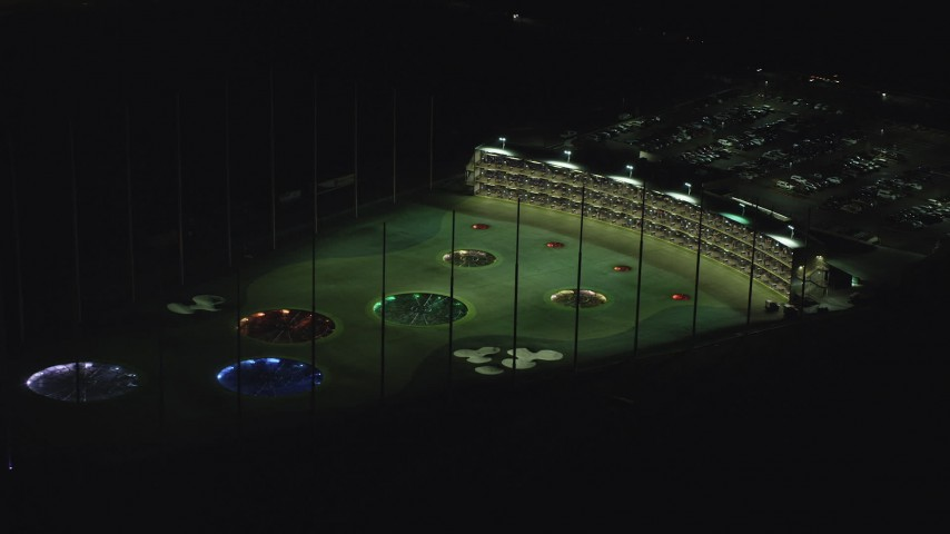 6K aerial video slowly flying by a Topgolf course in Hillsboro, Oregon at night Aerial Stock Footage | AX155_476