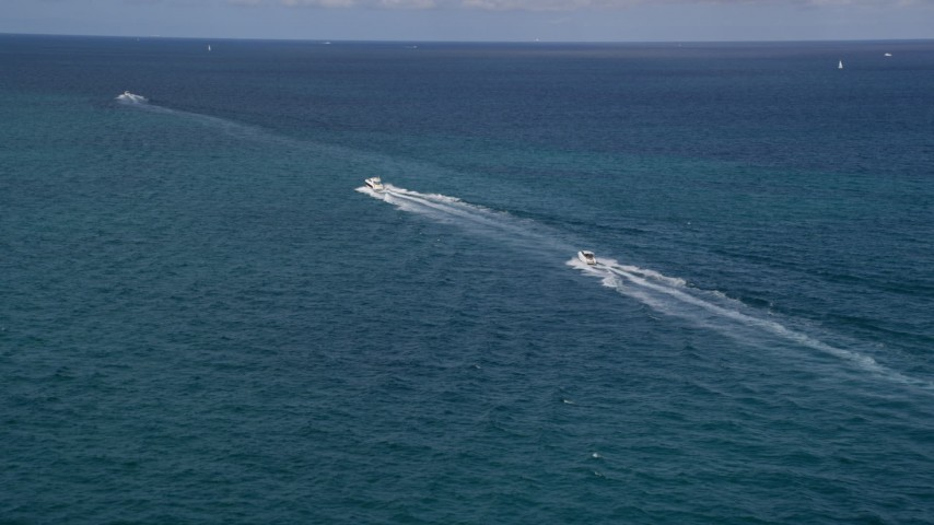 Approach Fishing Boats Racing across the Blue Water of the Ocean near South Beach, Florida Aerial Stock Footage | AX21_043
