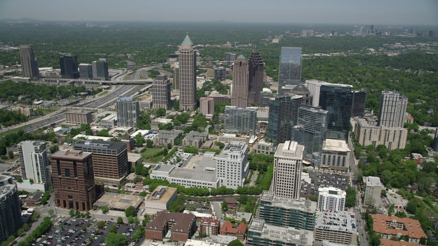 5K aerial video flying over office buildings toward skyscrapers, Midtown Atlanta, Georgia Aerial Stock Footage | AX36_011
