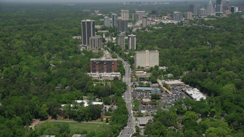 5K stock footage aerial video following Peachtree Road past office buildings among wooded area, Buckhead Aerial Stock Footage | AX36_049