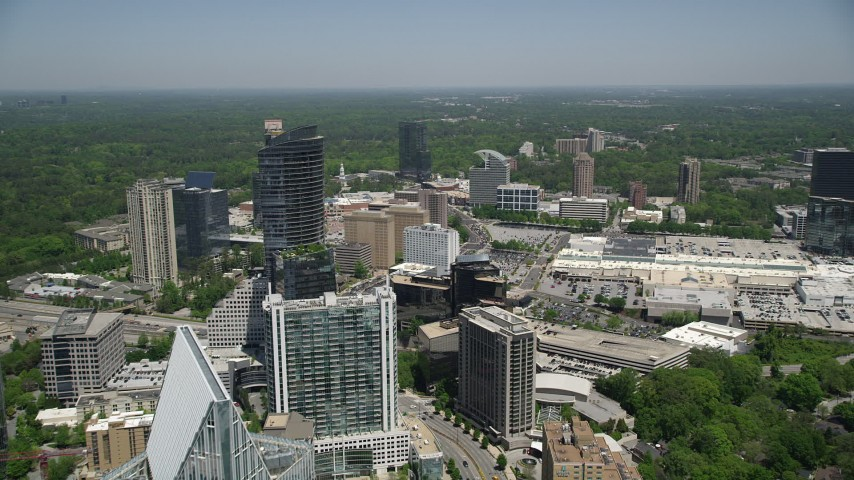 5K stock footage aerial video flying by skyscrapers and office buildings toward a shopping center, Buckhead, Georgia Aerial Stock Footage | AX36_069