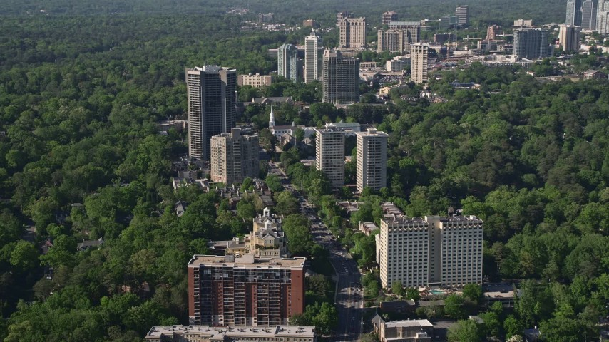 5K stock footage aerial video following Peachtree Road through condominium complexes and trees, Buckhead, Georgia Aerial Stock Footage | AX38_009