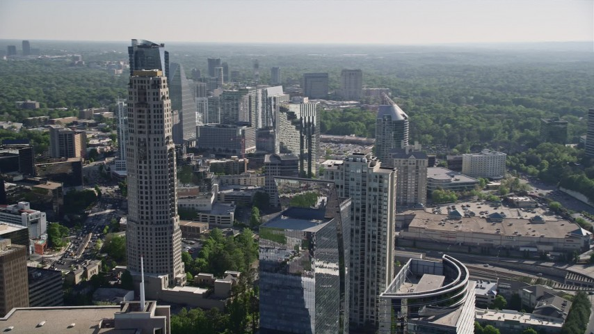 5K stock footage aerial video tilting down from skyscrapers to Marsh Mercer building, Buckhead, Georgia Aerial Stock Footage | AX38_018