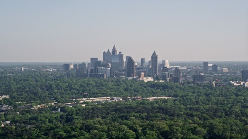 5K stock footage aerial video of a distant shot of Midtown Atlanta skyscrapers beyond trees, Buckhead, Georgia Aerial Stock Footage | AX38_027