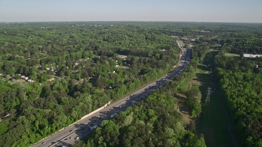 5K stock footage aerial video orbiting an interstate with heavy traffic bordered by trees, West Atlanta, Georgia Aerial Stock Footage | AX38_032
