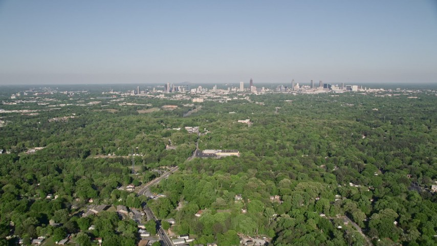 5K aerial video flying over a junkyard and trees, tilt up revealing Midtown Atlanta, Georgia Aerial Stock Footage | AX38_033