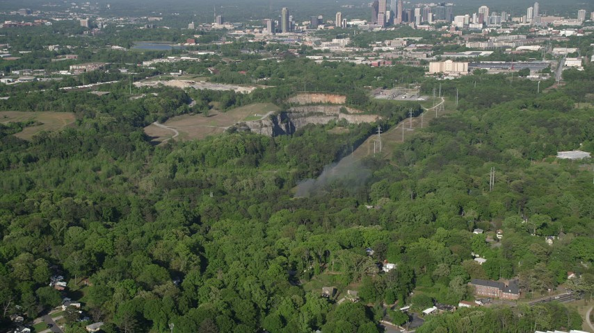 5K stock footage aerial video of smoke rising from a house on fire in a wooded neighborhood, West Atlanta Aerial Stock Footage | AX38_034