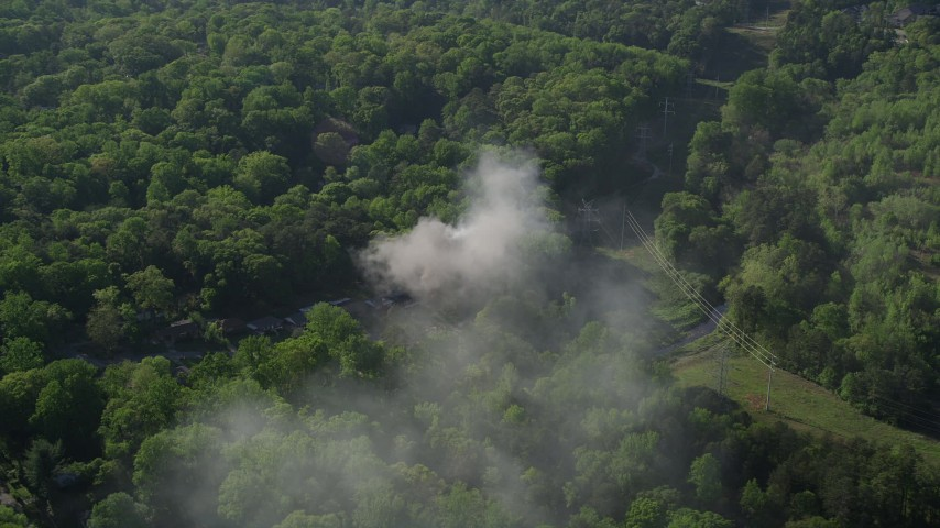5K stock footage aerial video orbiting smoke from a burning home in a wooded area, West Atlanta Aerial Stock Footage | AX38_036