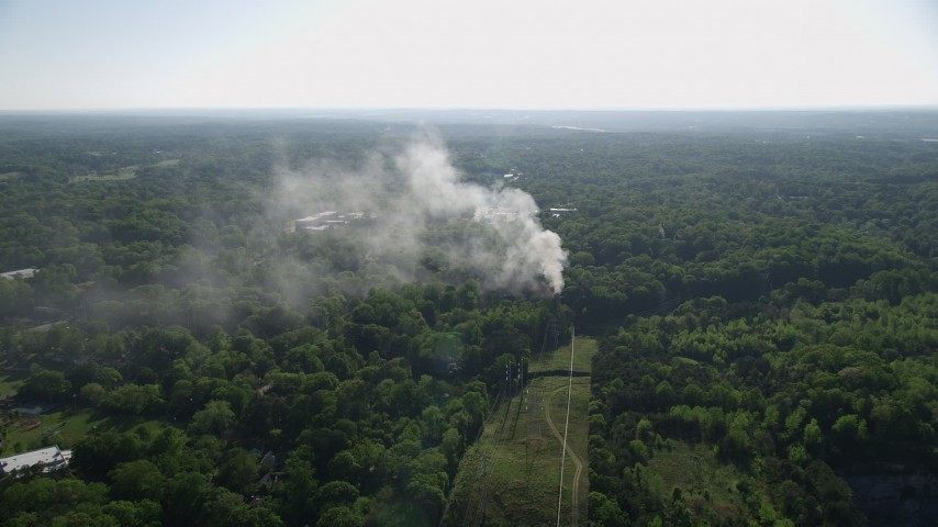 5K stock footage aerial video of smoke rising from a house fire in a wooded area, West Atlanta, Georgia Aerial Stock Footage | AX38_048