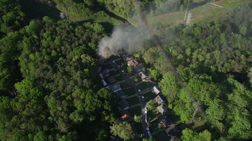 5K stock footage aerial video approaching smoke rising from a burning house in a wooded area, West Atlanta Aerial Stock Footage | AX38_049