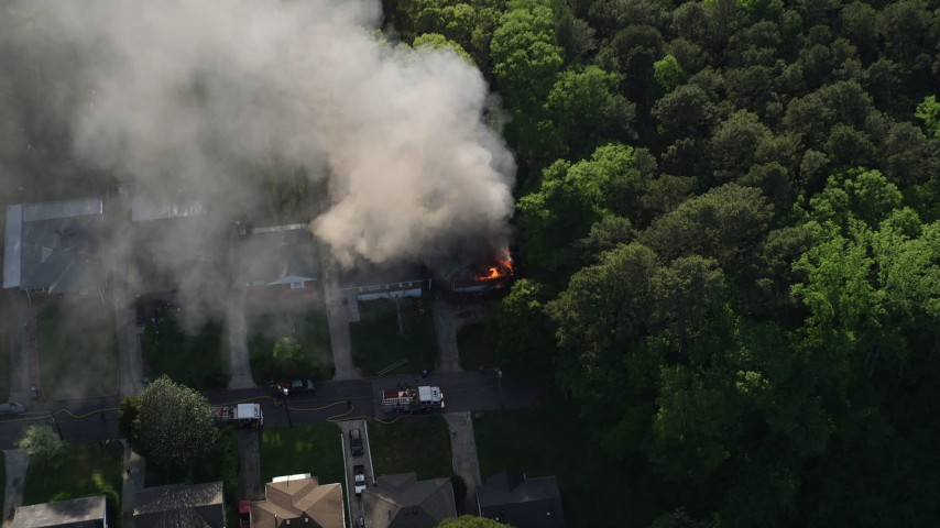 5K aerial video approaching a burning home with smoke rising and tilt down to a bird's eye, West Atlanta Aerial Stock Footage   AX38_053
