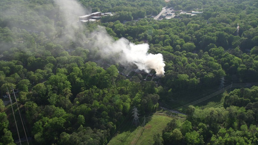 5K stock footage aerial video flying away from smoke from a burning house in a wooded area, West Atlanta Aerial Stock Footage | AX38_054