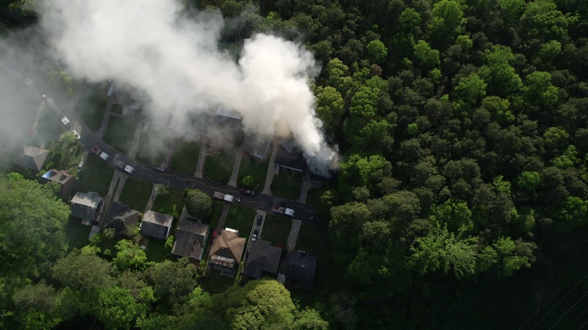 5K stock footage aerial video of a bird's eye of smoke rising from a burning house in a wooded area, West Atlanta Aerial Stock Footage | AX38_056