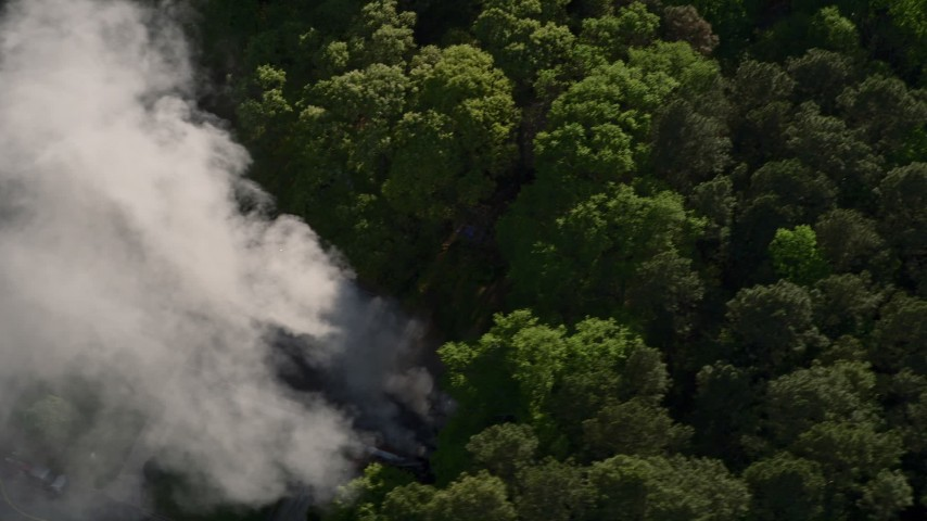 5K stock footage aerial video of smoke rising from a house fire in a wooded area, West Atlanta Aerial Stock Footage | AX38_058