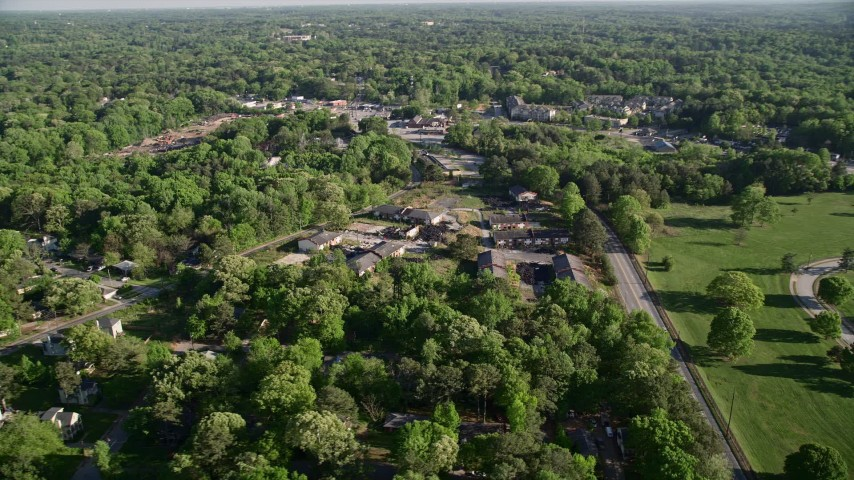 5K stock footage aerial video flying by abandoned buildings among trees, West Atlanta Aerial Stock Footage | AX38_082