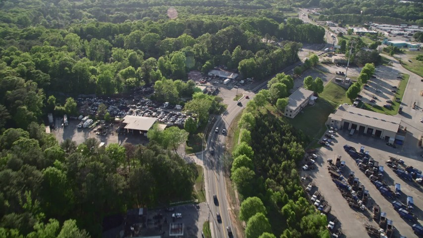 5K stock footage aerial video flying over a parkway and auto parts yard near trees, West Atlanta Aerial Stock Footage | AX38_083