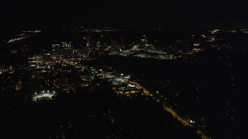 5K aerial video approaching city road and skyscrapers, Buckhead, Georgia, night Aerial Stock Footage | AX41_040