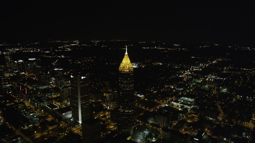5K stock footage aerial video tilting down from black sky to Bank of America Plaza, Midtown Atlanta, night Aerial Stock Footage | AX41_068