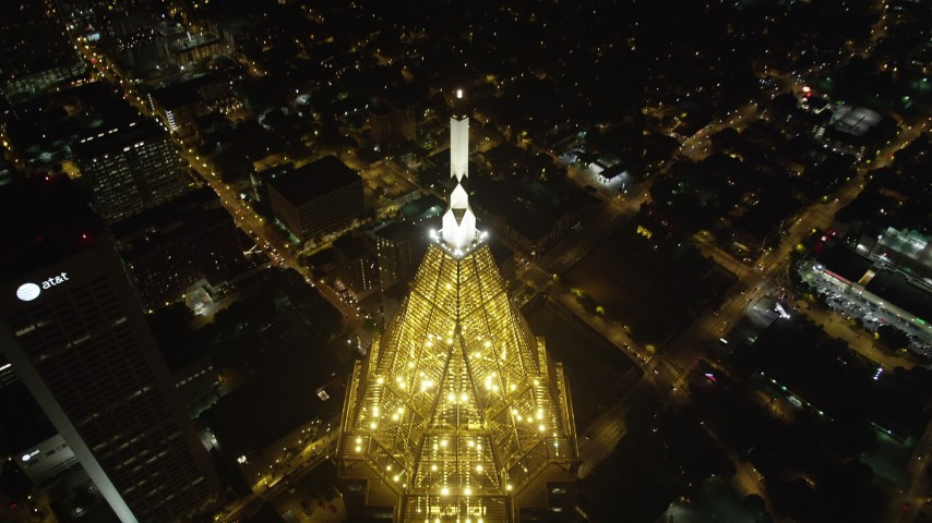 5K stock footage aerial video approaching Bank of America Plaza and tilt down to bird's eye of city streets, Midtown Atlanta, night Aerial Stock Footage | AX41_069