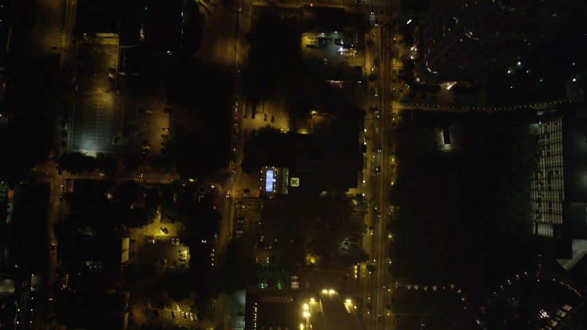 5K stock footage aerial video tilting down to bird's eye of GLG Grand and city streets, Midtown Atlanta, night Aerial Stock Footage | AX41_073