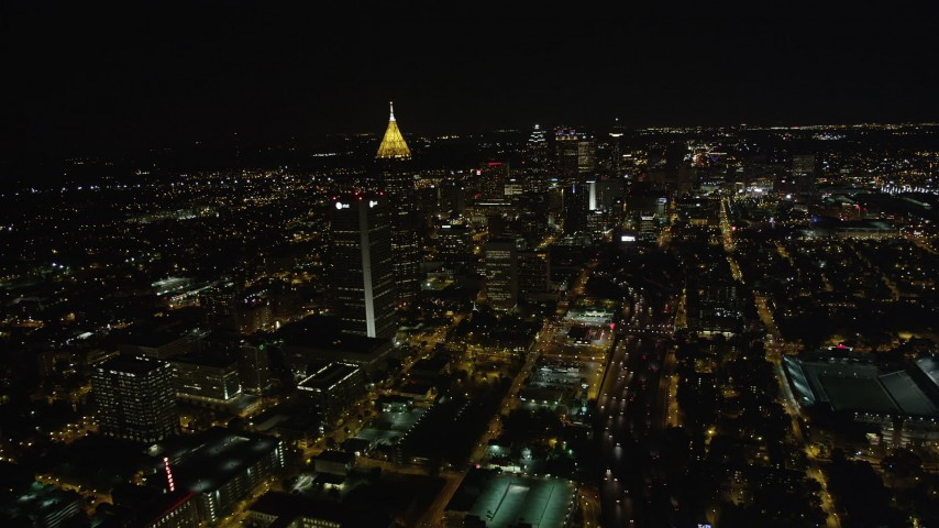 5K stock footage aerial video flying by skyscrapers toward downtown, Midtown Atlanta, Georgia, night Aerial Stock Footage | AX41_074