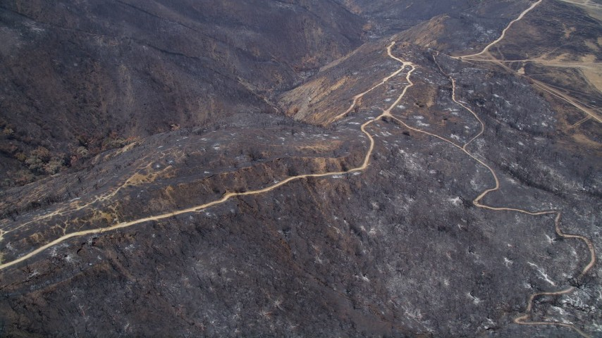 5K stock footage aerial video fly over fire damage on a mountain ridge with dirt roads, Santa Monica Mountains, California Aerial Stock Footage | AX42_001