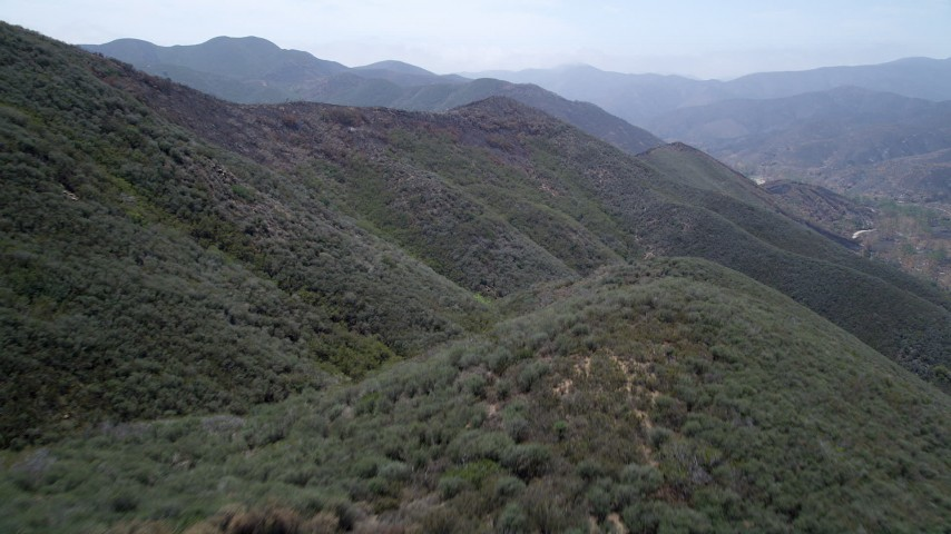 5K stock footage aerial video fly over slopes of Santa Monica Mountains damaged by wildfires, revealing vegetation, California Aerial Stock Footage | AX42_006