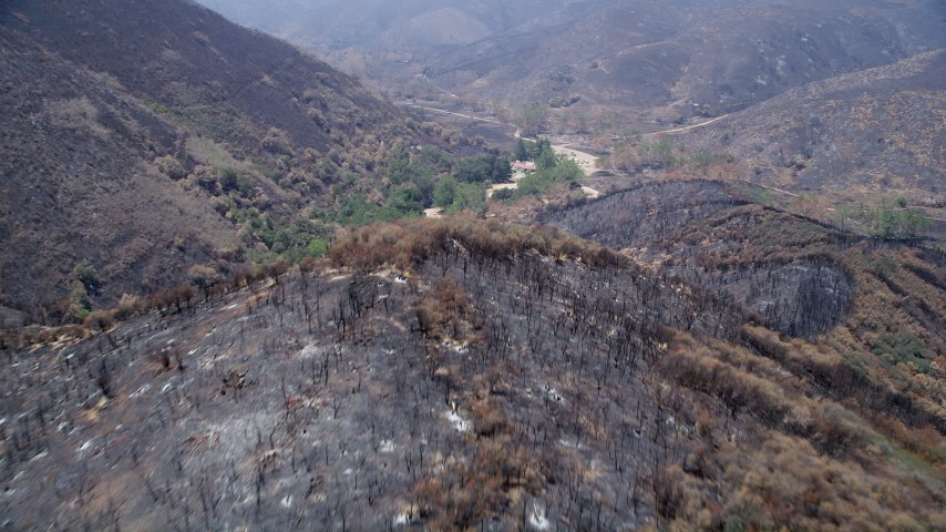 5K aerial video fly over scorched ridge of Santa Monica Mountains and approach an isolated rural home, California Aerial Stock Footage | AX42_008