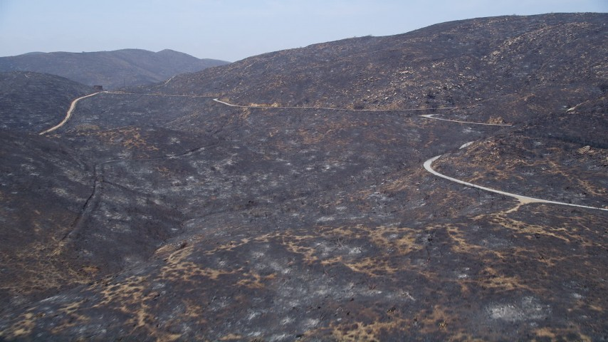 5K stock footage aerial video approach a mountain road winding around the fire-damaged slopes of Santa Monica Mountains, California Aerial Stock Footage | AX42_010