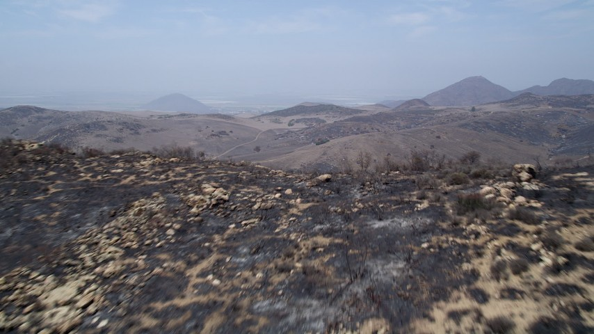 5K stock footage aerial video fly over a fire-damaged slope to reveal barren, less damaged Santa Monica Mountains, California Aerial Stock Footage | AX42_011