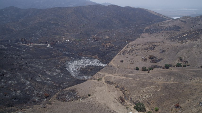 5K stock footage aerial video of burned rural homes near the edge of wildfire damage, Santa Monica Mountains, California Aerial Stock Footage | AX42_012