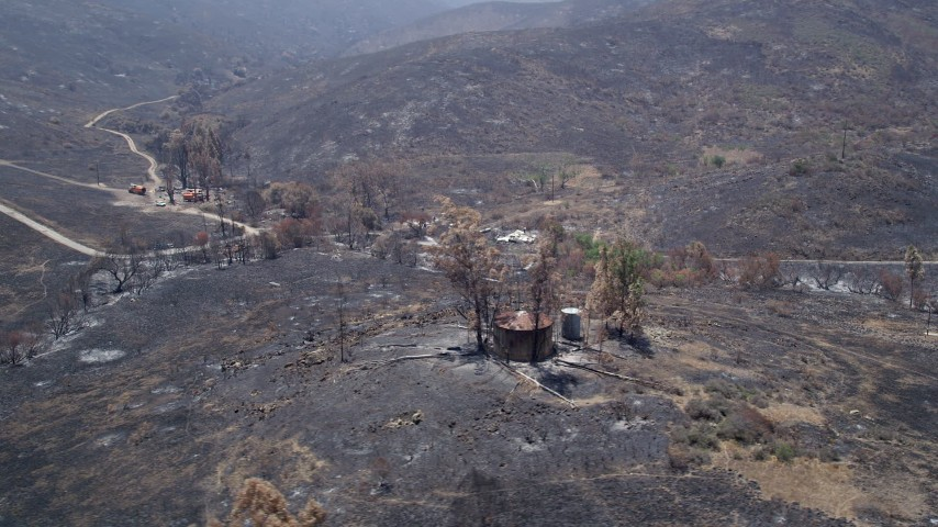 5K stock footage aerial video flyby fire-ravaged rural homes surrounded by wildfire damage in the Santa Monica Mountains, California Aerial Stock Footage | AX42_014